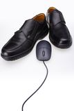 Black shoes and computer mouse. Detail of men's black dress shoes and a black computer mouse. White background royalty free stock images