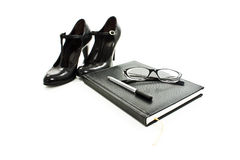 Black shoes, eyeglasses and pen on book Royalty Free Stock Photo