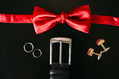 Black shoes of the groom, red bow tie, cufflinks, belt, on a bla Stock Photo