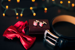 Black shoes of the groom, red bow tie, cufflinks, belt, on a bla Stock Images