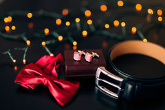 Black shoes of the groom, red bow tie, cufflinks, belt, on a bla Royalty Free Stock Images
