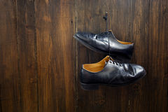 Black shoes  hanging on the nail over wooden background Royalty Free Stock Photography