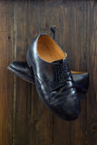 Black shoes  hanging on the nail over wooden background Royalty Free Stock Image