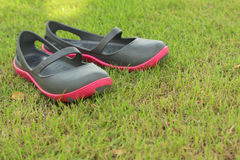 Black shoes lying on the green grass. Royalty Free Stock Photos