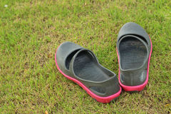 Black shoes lying on the green grass. Royalty Free Stock Image