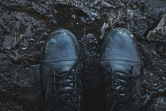Black shoes in the mud. View from above stock photography