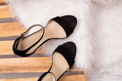 Black shoes on a pallet, white fur. Fashionable concept Royalty Free Stock Image