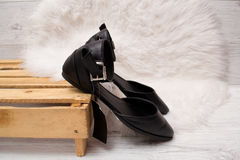 Black shoes on a pallet, white fur. Fashionable concept Royalty Free Stock Photography