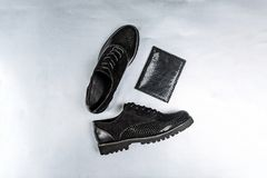 Trendy black shoes and a patent leather wallet with a snake-skin pattern on a white paper background royalty free stock photography