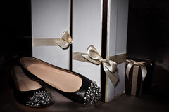 Black shoes with spikes and gift boxes Stock Photos