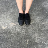 Black Shoes Standing on the Concrete Floor Royalty Free Stock Image