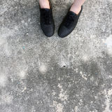 Black Shoes Standing on the Concrete Floor Royalty Free Stock Photos
