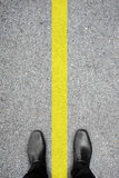 Black shoes standing on the floor and yellow line. Black shoes standing on the asphalt concrete floor and yellow line between his legs like he is on both side Stock Photography