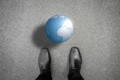 Black shoes standing in front of the earth. Black shoes standing on the asphalt concrete floor in front of the earth Royalty Free Stock Images