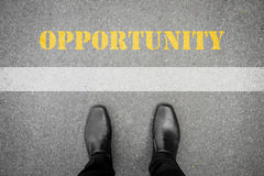 Black shoes standing in front of opportunity. Black shoes standing on the asphalt concrete floor in front of white line of opportunity Stock Images