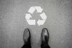 Black shoes standing in front of recycle symbol Royalty Free Stock Images