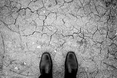 Black shoes standing on ground crack Stock Photography