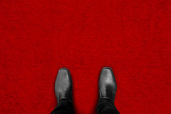 Black shoes standing on red carpet. Floor - begin his success and fame Royalty Free Stock Images