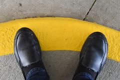 Black shoes standing on a yellow painted sidewalk curb stock photo