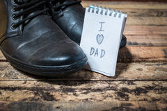 Black shoes with word love dad. On notebook Royalty Free Stock Photo