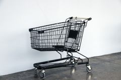 Black shopping Cart on the floor and white background. trolley is a cart supplied by a shop. Black shopping Cart on the floor and white background. trolley is a Royalty Free Stock Photography