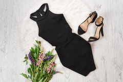 Black short dress and shoes on white fur, a bouquet of flowers. Fashionable concept Stock Photo