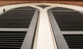 Black shutters on church building. Abstract view of closed black shutters on church building. Represents a path that splits Stock Photo