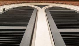 Black shutters on church building Stock Photo