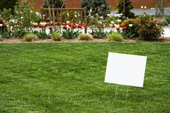 Black Sign on Lawn. With copy space and background of bench and flowers. Horizontal Royalty Free Stock Image