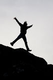 Black silhouette of a boy jumping from a rock with open arms. Black silhouette of a boy jumping from a rock on white background Stock Image