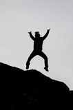 Black silhouette of a boy jumping from a rock with open arms Royalty Free Stock Image
