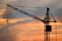 Black silhouette of a construction crane at dusk, dawn stock image