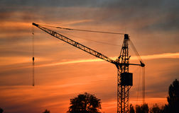 Black silhouette of a construction crane at dusk, dawn royalty free stock photos