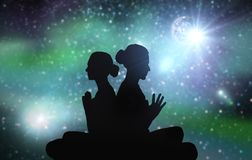 Black silhouette of couple meditating over space Stock Images