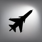 The black silhouette of a fighter plane. Stock Image
