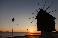 Black silhouette in the morning sun. Old windmill, Nessebar. Black silhouette in the morning sun. Old wooden windmill on the coast, the most popular landmark of stock image
