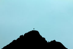 Black silhouette of mountain peak with summit cross. Blue background. Royalty Free Stock Photos