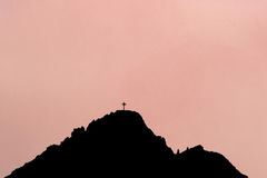 Black silhouette of mountain peak with summit cross. Rose background. Graphical black silhouette of mountain peak with summit cross. Rosy glowing background Royalty Free Stock Image