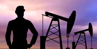 Black silhouette of oil worker and pump jack. Industry, oilfield, people and development concept - black silhouette of oil worker and pump jack Royalty Free Stock Images