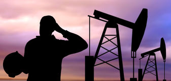 Black silhouette of oil worker and pump jack. Industry, oilfield, people and development concept - black silhouette of oil worker and pump jack Stock Photo
