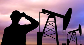 Black silhouette of oil worker and pump jack. Industry, oilfield, people and development concept - black silhouette of oil worker and pump jack Stock Image