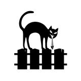Black silhouette of the sitting cat on a fence. Stock Photo