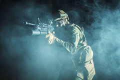 Black silhouette of soldier. Image of soldier in the smoke moving in battle operation. Back light, cropped, toned and colorized Stock Photos