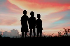 Black silhouette of three children standing together. stock photos