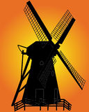 Black silhouette of a windmill. On an orange background Royalty Free Stock Image