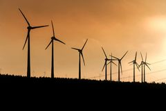 Black Silhouette of windturbines energy generator on amazing sunset at a wind farm in germany Stock Photos