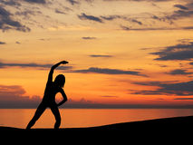 A black silhouette of a woman doing exercise on a sunset Stock Photo