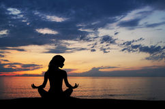 A black silhouette of a woman doing yoga on a sunset Royalty Free Stock Photography