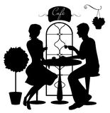 Black silhouettes of boy and girl in cafe Stock Photo