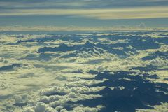 Black silhouettes of the Himalayan mountains stick out of the white valley of clouds under the blue sky aerial view. A black silhouettes of the Himalayan stock photo